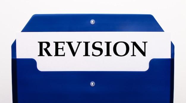 白い背景の上に、紙のための青いフォルダー。フォルダには、revisionという単語が書かれた1枚の紙があります