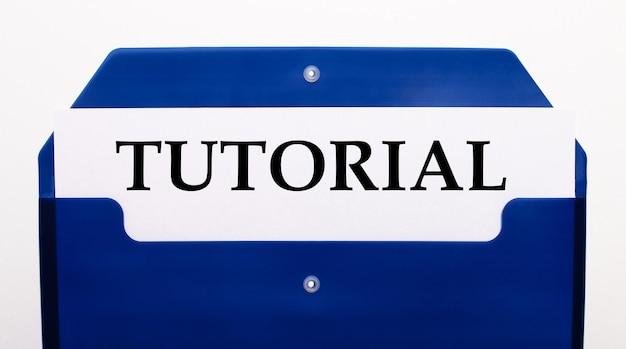 白い背景に、紙の青いフォルダー。フォルダーには、「チュートリアル」という単語が記載された1枚の紙があります。