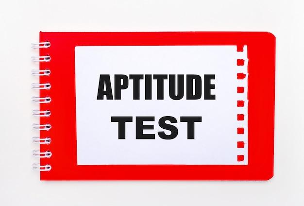 На белом фоне - ярко-красный блокнот на спирали. на нем белый лист бумаги с текстом тест на аптитуду.