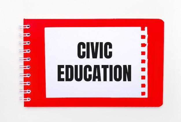 白い背景-らせん状の真っ赤なノート。その上にciviceducationというテキストが書かれた白い紙があります