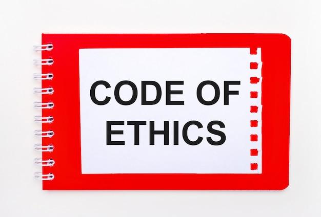 白い背景-らせん状の真っ赤なノート。その上に「倫理規定」というテキストが書かれた白い紙があります。