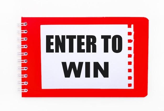 На белом фоне - ярко-красная тетрадь по спирали. на нем белый лист бумаги с надписью enter to win.