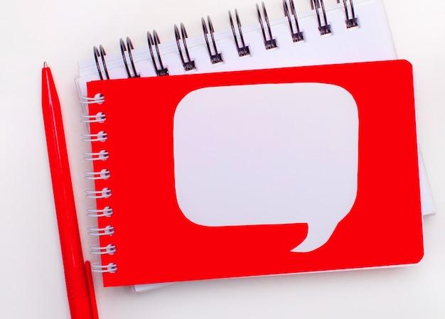 白い背景に、赤いペン、白と赤のノート、テキストを挿入する場所のある白いカーリーカード。
