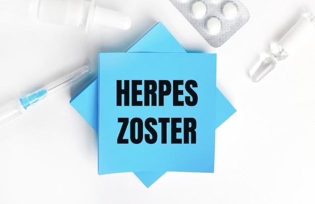 白い背景に、注射器、アンプル、錠剤、薬瓶、帯状疱疹の刻印が入った水色のステッカー。医療の概念