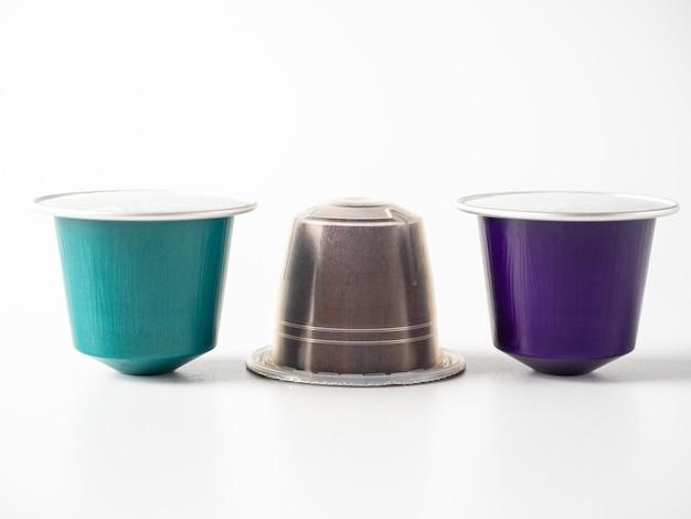 白い背景には、コーヒーマシン用の芳香性の挽いたコーヒーが入ったさまざまなカプセルがあります。そのうちの2つはリサイクルに適したアルミニウムで、1つはプラスチック製です。側面図。