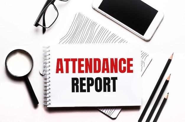 白い背景のメガネ、拡大鏡、鉛筆、スマートフォン、ノートに「出席レポート」というテキストが表示されます