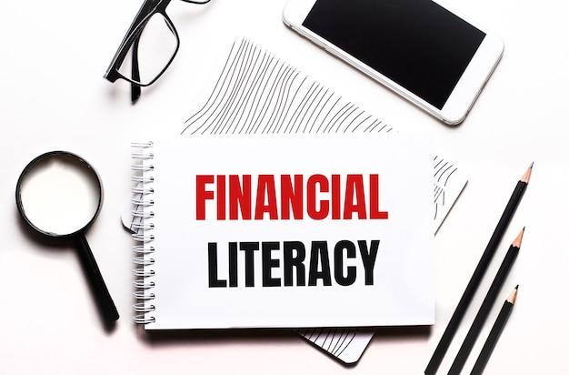 白い背景のメガネ、拡大鏡、鉛筆、スマートフォン、ノートにfinancialliteracyというテキストが表示されます