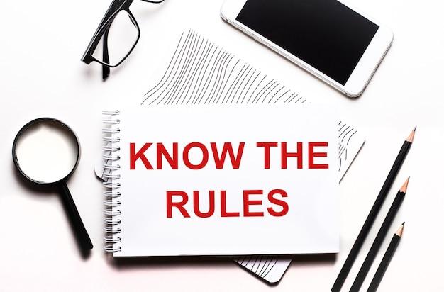 На белом фоне очки, лупа, карандаши, смартфон и блокнот с текстом знай правила