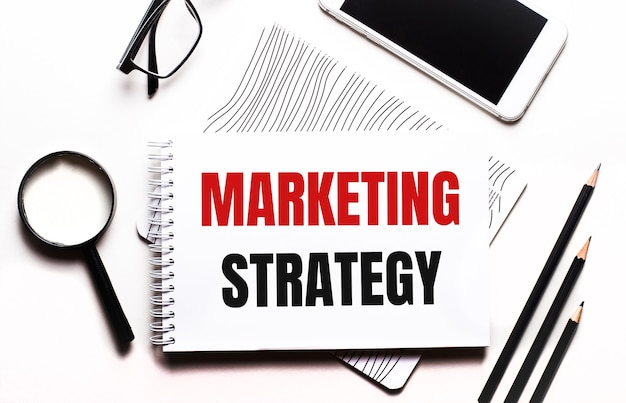 На белом фоне очки, лупа, карандаши, смартфон и блокнот с текстом маркетинговая стратегия.