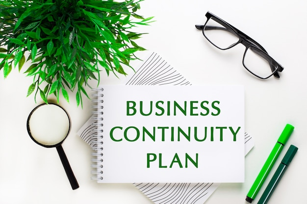 白い背景の上に、business continuity plan、メガネ、虫眼鏡、緑色のマーカー、緑色の植物という言葉が書かれたノートがあります。