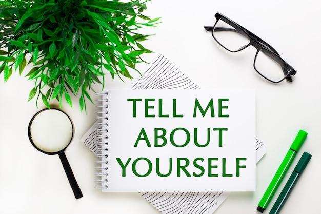 白い背景の上に、「自分について教えて」という言葉が書かれたノート、メガネ、虫眼鏡、緑色のマーカー、緑色の植物があります。