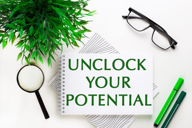 흰색 배경에는 unlock your potential, 안경, 돋보기, 녹색 마커 및 녹색 식물이라는 단어가 적힌 노트북이 있습니다.