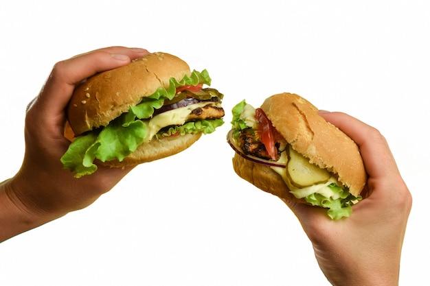 На белом фоне по два бутерброда в каждой руке с мясом, сыром, помидорами, луком, огурцами и салатом.