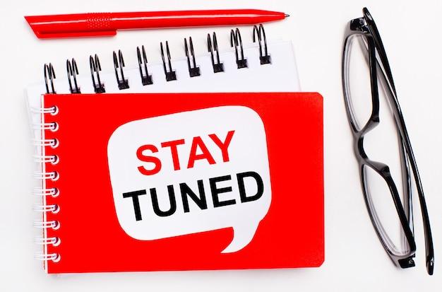 白地に、白と赤のメモ帳、黒のメガネ、赤のペン、白のカードに「staytuned」というテキストが表示されます。