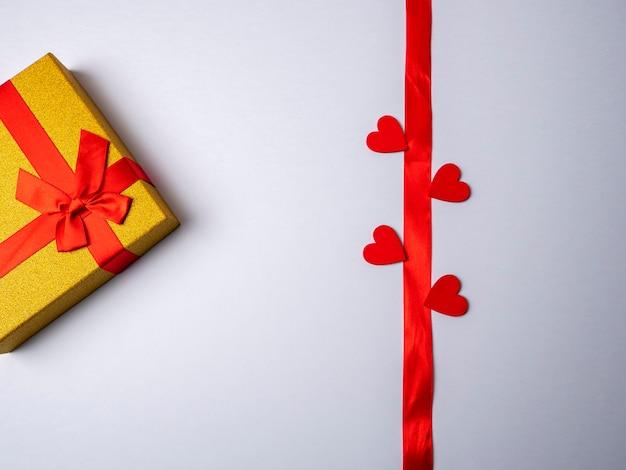 На белом ярком фоне лежит длинная красная лента в окружении четырех сердечек и рядом с желтым подарком с красной лентой.