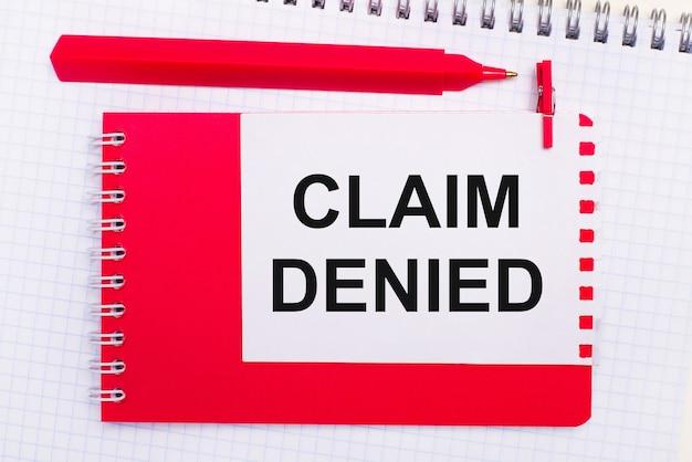 На белом блокноте красная ручка, красный блокнот и белый лист бумаги с текстом претензия отказана.