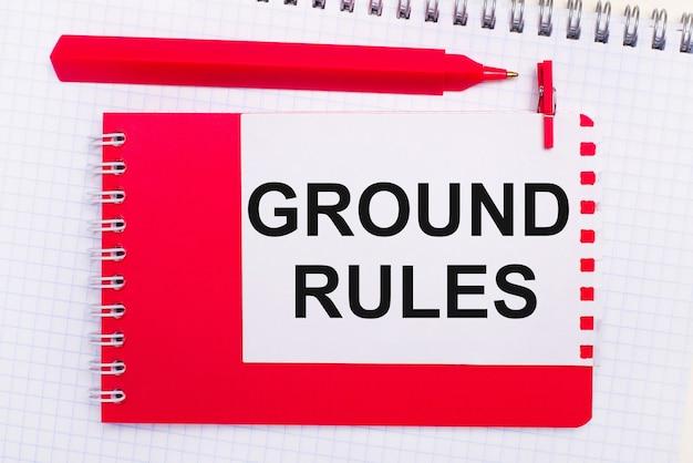 На белом блокноте красная ручка, красный блокнот и белый лист бумаги с текстом основные правила.