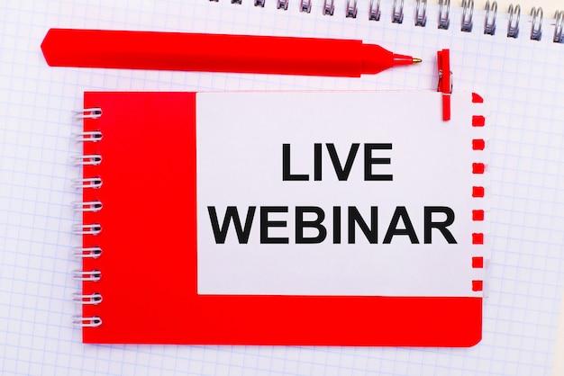 На белом блокноте красная ручка, красный блокнот и белый лист бумаги с текстом live webinar.