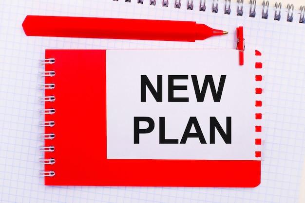 На белом блокноте красная ручка, красный блокнот и белый лист бумаги с текстом новый план.