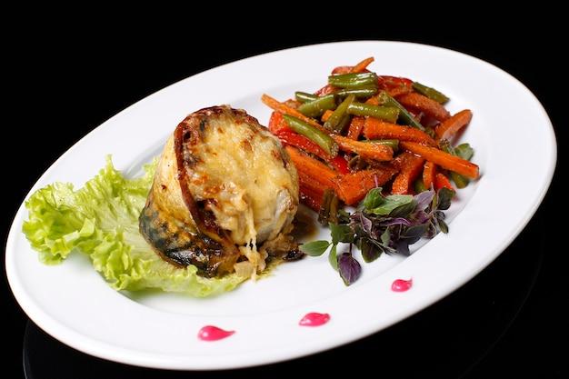 하얀 접시에 고등어를 치즈에 튀긴 것과 야채를 익힌 것. 녹색 콩, 당근, 바질, 샐러드., 검정색 배경에. 고등어 튀김