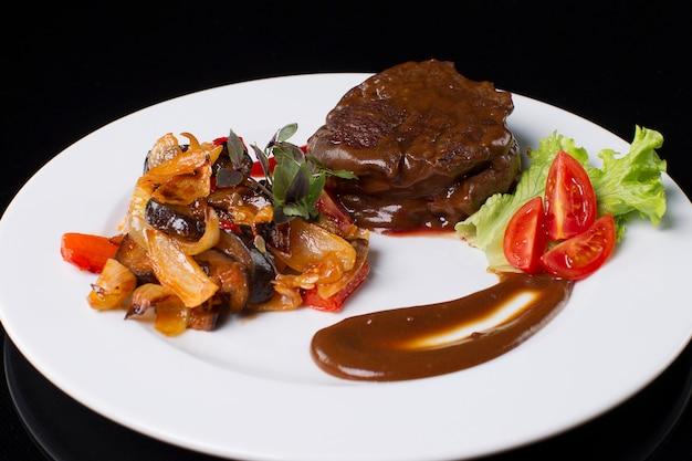 На белой тарелке жареное мясо с подливой, тушеные овощи, листья салата, соус, нарезанный базилик и помидор. говядина в соусе.