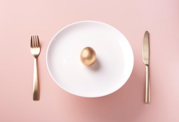 На белой тарелке лежит золотое яйцо, рядом с золотыми столовыми приборами на пудровом фоне.