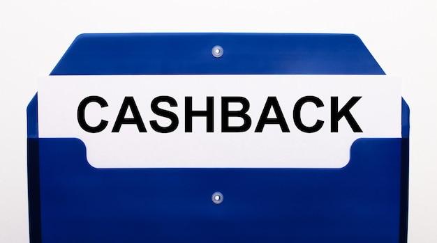На белой поверхности синяя папка для бумаг. в папке лежит лист бумаги с надписью cashback.