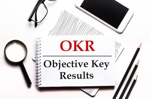 На белой поверхности очки, лупа, карандаши, смартфон и блокнот с текстом okr objective key results.