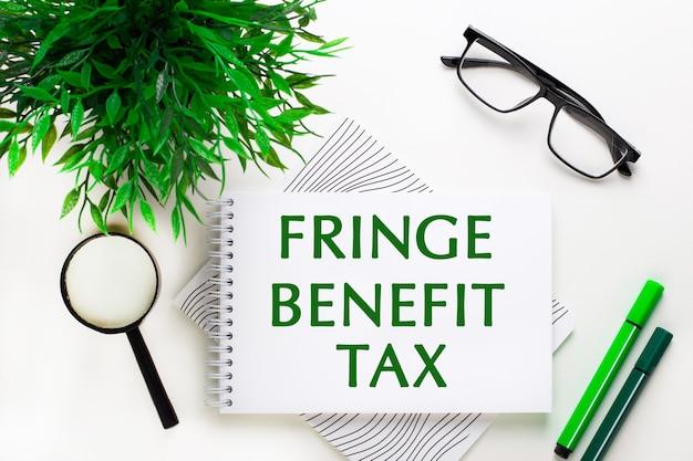흰색 표면에는 fringe benefit tax, 안경, 돋보기, 녹색 마커 및 녹색 식물이 적힌 노트북이 있습니다.