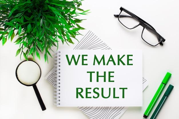 白い表面には、「結果を出す」という言葉が書かれたノート、メガネ、虫眼鏡、緑色のマーカー、緑色の植物があります。