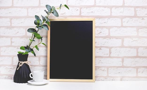 明るいレンガの壁を背景にした白いテーブル、暗い花瓶にユーカリの枝、白いカップ、テキストを挿入する場所のある明るい木製のフレーム。ホームオフィス。コピースペース