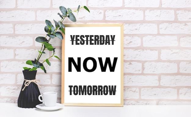 На белом столе на фоне светлой кирпичной стены ветка эвкалипта в темной вазе, белая чашка и светлая деревянная рамка с надписью вчера сейчас завтра. интерьер домашнего офиса.