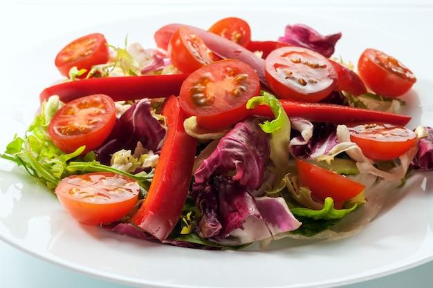 白い皿の白いテーブルの上に新鮮な野菜のサラダがあります