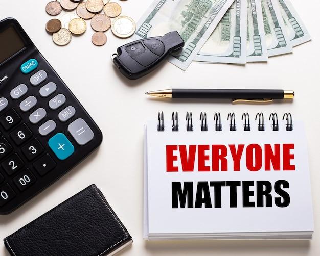 흰색 테이블에는 계산기, 자동차 열쇠, 현금, 펜 및 everyone matters라는 문구가 적힌 노트북이 있습니다.