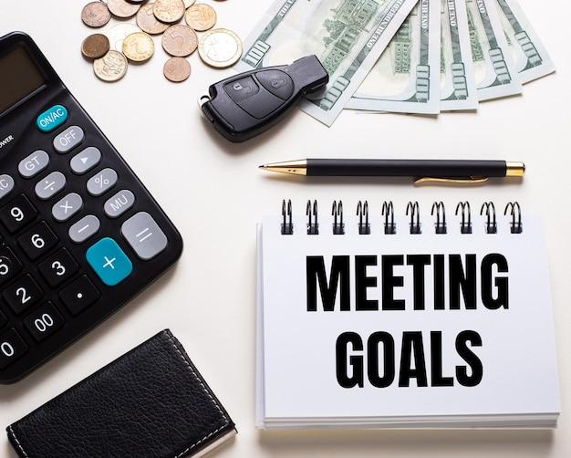 На белом столе калькулятор, ключ от машины, деньги, ручка и блокнот с надписью meeting goals.