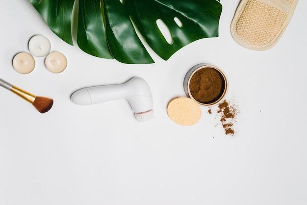 白いテーブルの上には、顔の皮膚をきれいにするための電動ブラシ、緑の葉、コーヒースクラブ、ブラシがあります