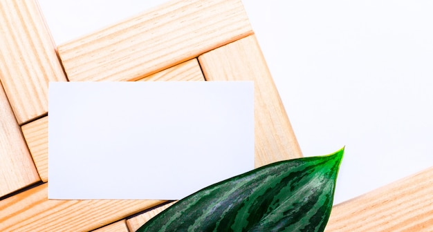 白いテーブルの木製のビルディングブロック、テキストを挿入する場所と植物の緑の葉が付いた白い空白のカード。テンプレート。コピースペースのある上面図
