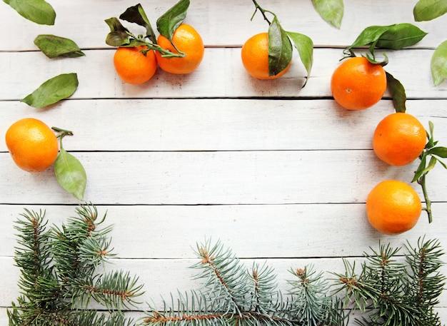 흰색 나무 배경에는 잎과 침엽수 전나무가 있는 잘 익은 오렌지 감귤이 놓여 있습니다