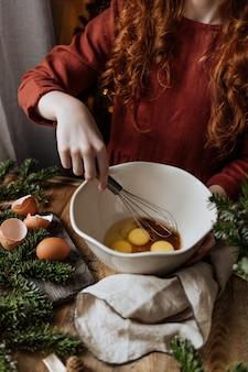 겨울 휴가에 빨간 머리 소녀가 그릇에 계란과 설탕을 섞습니다.