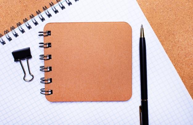 木製の背景に、ノート、黒いペン、ペーパークリップ、テキストを挿入する場所のある茶色のノート。テンプレート。ビジネスコンセプト