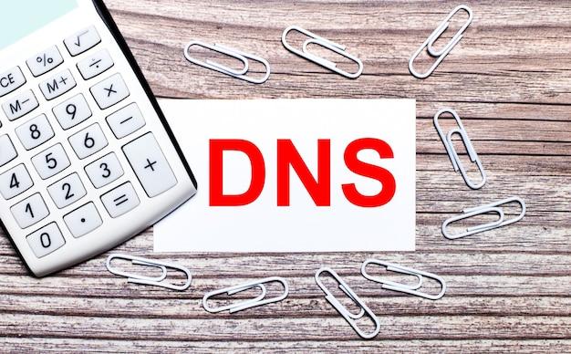 На деревянном фоне белый калькулятор, белые скрепки и белая карточка с текстом dns domain name system. вид сверху.