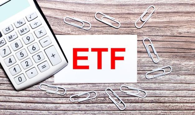 На деревянном фоне белый калькулятор, белые скрепки и белая карточка с текстом etf exchange traded funds. вид сверху.