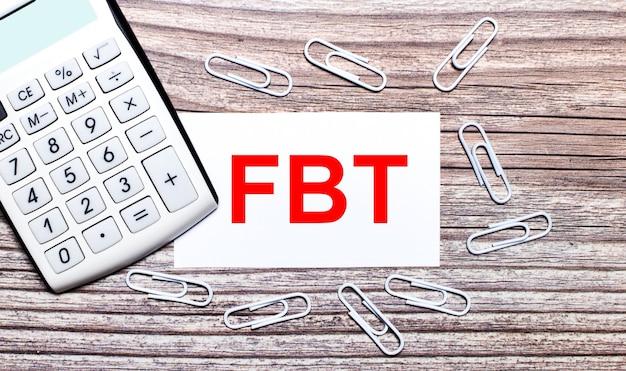 На деревянном фоне белый калькулятор, белые канцелярские скрепки и белая карточка с текстом fbt fringe benefit tax. вид сверху.
