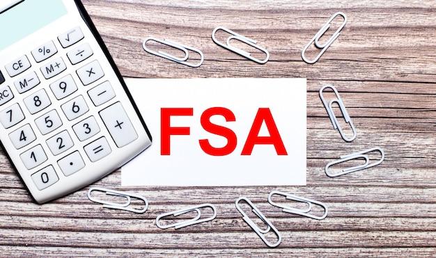 На деревянном фоне белый калькулятор, белые скрепки и белая карточка с текстом fsa flexible spending account. вид сверху.