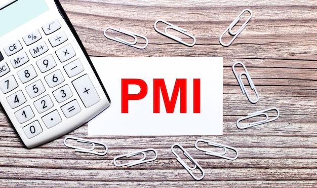 На деревянном фоне белый калькулятор, белые скрепки и белая карточка с текстом pmi project management institute. вид сверху.