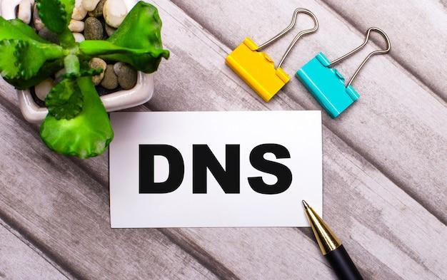 На деревянном фоне белая карточка с текстом dns domain name system, желто-зеленые скрепки и растение в горшке. вид сверху Premium Фотографии