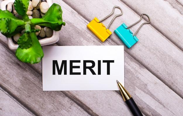 木製の背景に、meritというテキストが書かれた白いカード、黄色と緑色のペーパークリップ、鉢植えの植物。上から見る