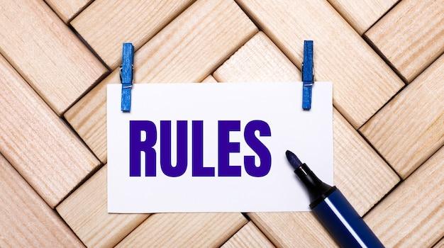 На деревянном фоне белая карточка с текстом правила на синих прищепках и синим маркером. вид сверху