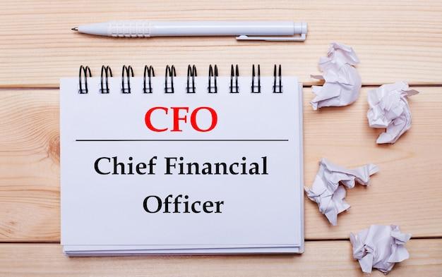 На деревянном фоне белая записная книжка с надписью cfo chief financial officer, белая ручка и скомканные белые листы бумаги.