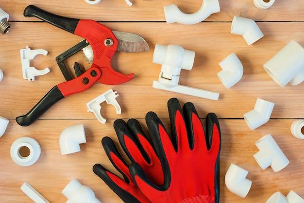 木製の背景には、プラスチックパイプを修理するためのツールがあります。